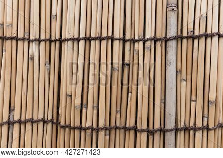 Bamboo Fence With Brown Rope Texture Background. Tree Fence Close Up View