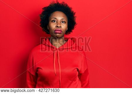 Young african american woman wearing casual sweatshirt relaxed with serious expression on face. simple and natural looking at the camera.