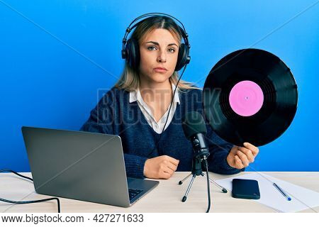 Young caucasian woman working at radio studio holding vinyl disc thinking attitude and sober expression looking self confident