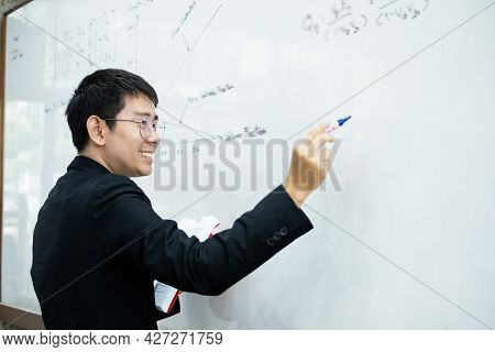 An Asian Male Teacher In A Classroom Near The Whiteboard Is Writing And Teaching A Lesson With A Spe