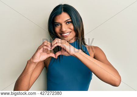 Young latin transsexual transgender woman wearing casual clothes smiling in love doing heart symbol shape with hands. romantic concept.