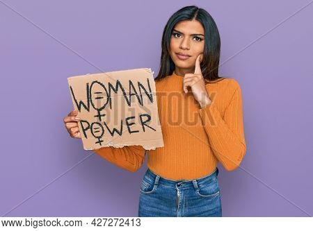 Young latin transsexual transgender woman holding woman power banner serious face thinking about question with hand on chin, thoughtful about confusing idea