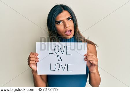 Young latin transsexual transgender woman holding paper with love is love message in shock face, looking skeptical and sarcastic, surprised with open mouth