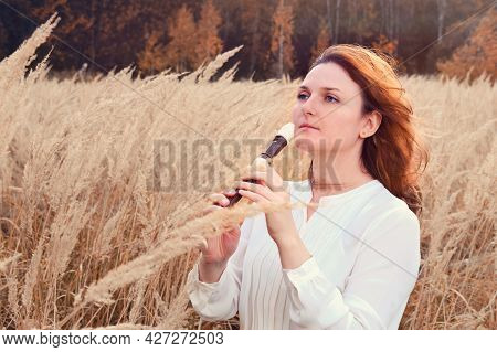 A Young Woman Plays A Flute Standing In A Field Near Forest Trees