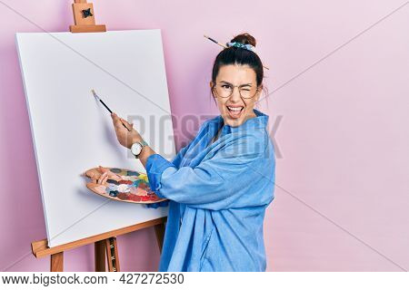 Young hispanic woman standing drawing with palette by painter easel stand winking looking at the camera with sexy expression, cheerful and happy face.