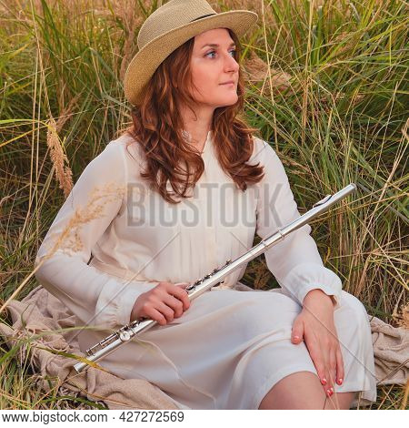 A Young Woman Musician With A Flute Among The Yellow Autumn Grass