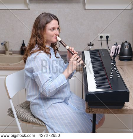 A Female Musician With A Flute In Her Hands Conducts Online Music Training Over The Phone