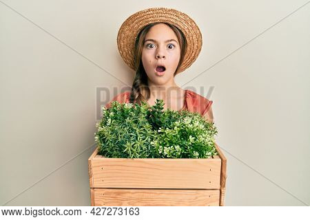 Beautiful brunette little girl wearing gardener hat holding wooden plant pot afraid and shocked with surprise and amazed expression, fear and excited face.