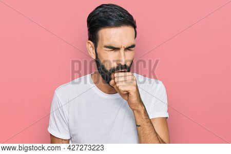 Young hispanic man wearing casual white t shirt feeling unwell and coughing as symptom for cold or bronchitis. health care concept.