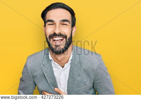 Young hispanic man wearing business clothes smiling and laughing hard out loud because funny crazy joke with hands on body.