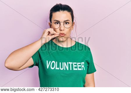 Young hispanic woman wearing volunteer t shirt mouth and lips shut as zip with fingers. secret and silent, taboo talking