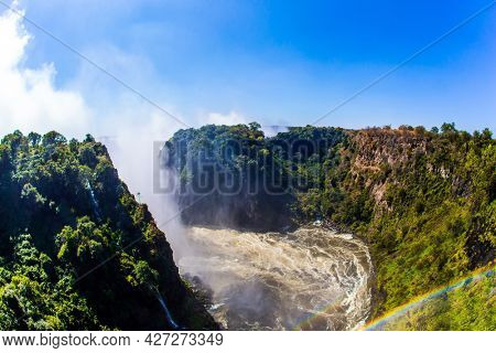 Huge rainbow in the water mist over the Victoria Falls. Giant cloud of water fog over a huge waterfall. Victoria Park, Zambezi River. Journey after the wet season. Concept of extreme and photo tourism