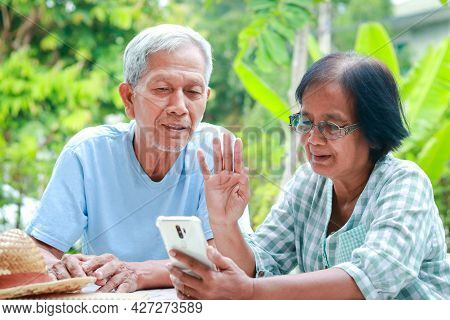Asian Elderly Couple Happy Living At Home Sitting In The Garden Holding A Smartphone, Chatting Onlin