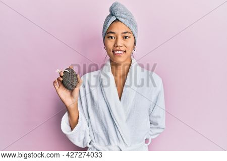 Young chinese woman wearing shower towel cap and bathrobe holding pumice stone looking positive and happy standing and smiling with a confident smile showing teeth