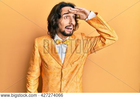 Young hispanic man wearing hipster elegant look very happy and smiling looking far away with hand over head. searching concept.