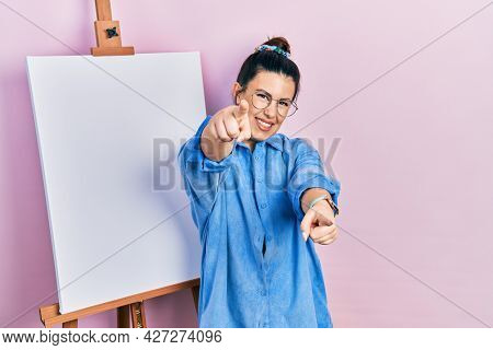 Young hispanic woman standing by painter easel stand pointing to you and the camera with fingers, smiling positive and cheerful