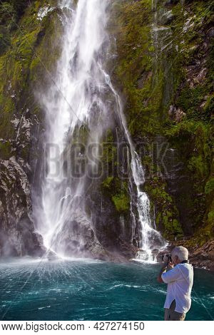 Magnificent powerful waterfall crashes down from the cliff of Milford Sound fjord. Magical trip to New Zealand