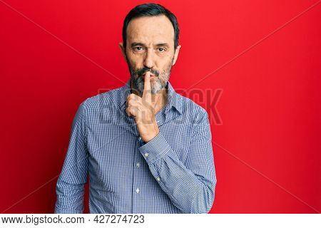 Middle age hispanic man wearing casual clothes asking to be quiet with finger on lips. silence and secret concept.