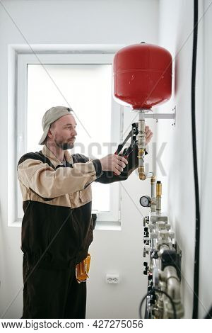 Repairman in workwear fixing part of pipe in new apartment