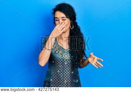Young woman wearing bindi and traditional kurta dress smelling something stinky and disgusting, intolerable smell, holding breath with fingers on nose. bad smell