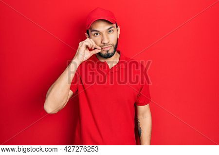 Hispanic man with beard wearing delivery uniform and cap mouth and lips shut as zip with fingers. secret and silent, taboo talking