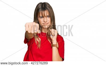 Teenager caucasian girl wearing casual red t shirt punching fist to fight, aggressive and angry attack, threat and violence