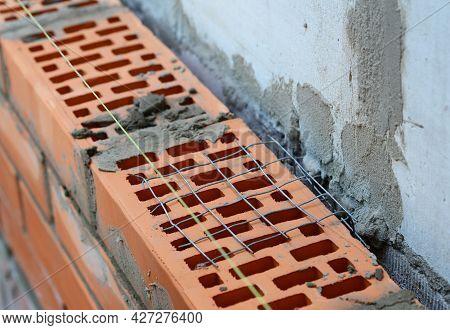 Wall Ties In Brick Masonry. A Close-up Of A Masonry Wall Tie, Mesh Wall Wire To Bond Face Brickwork,
