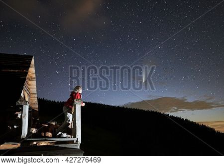 Young Woman In The Mountains Enjoying Beautiful Starry Night And A Comet From A Wooden Hut Porch. Co