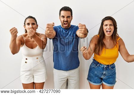 Group of young hispanic people standing over isolated background angry and mad raising fists frustrated and furious while shouting with anger. rage and aggressive concept.