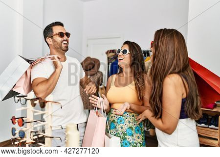Group of young hispanic people smiling happy trying on sunglasses at clothes store.