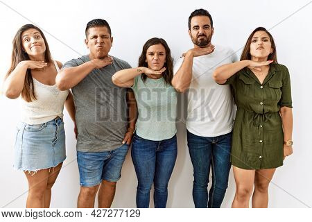 Group of young hispanic friends standing together over isolated background cutting throat with hand as knife, threaten aggression with furious violence