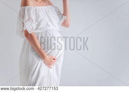 Close-up A Young Pregnant Woman In Anticipation Of A Baby In A White Hat, Dress, Hugs Her Belly. Ten