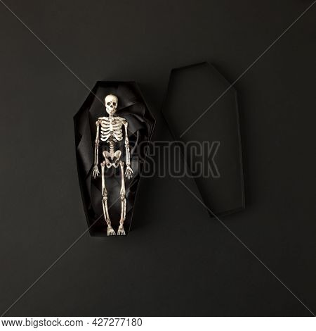 Toy Skeleton Of Man In Papercraft Coffin On Black Background, Stylish Monochrome Halloween Concept,