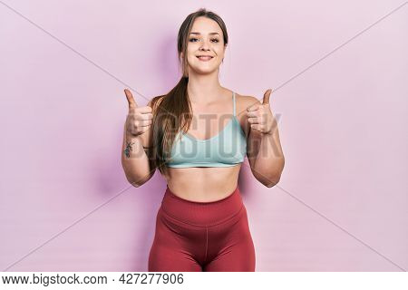 Young hispanic girl wearing sportswear success sign doing positive gesture with hand, thumbs up smiling and happy. cheerful expression and winner gesture.