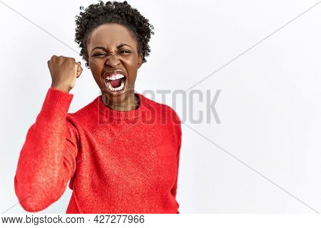 Young african american woman wearing casual clothes over isolated background angry and mad raising fist frustrated and furious while shouting with anger. rage and aggressive concept.