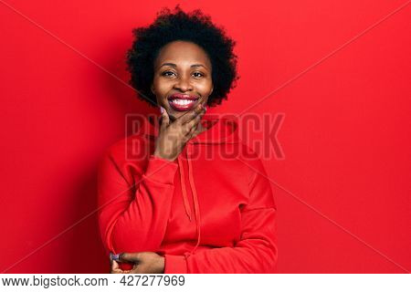 Young african american woman wearing casual sweatshirt looking confident at the camera smiling with crossed arms and hand raised on chin. thinking positive.