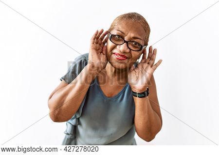 Mature hispanic woman wearing glasses standing over isolated background trying to hear both hands on ear gesture, curious for gossip. hearing problem, deaf