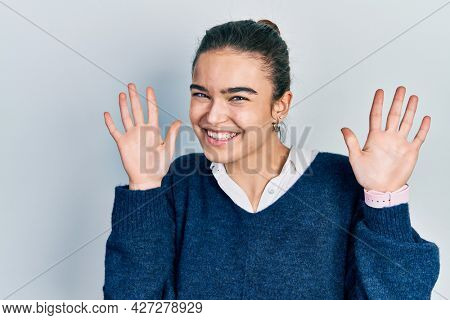 Young caucasian girl wearing casual clothes showing and pointing up with fingers number ten while smiling confident and happy.