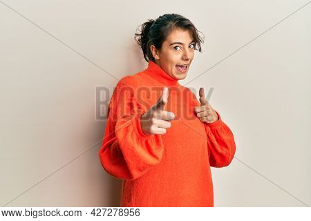 Young hispanic woman wearing casual winter sweater pointing fingers to camera with happy and funny face. good energy and vibes.