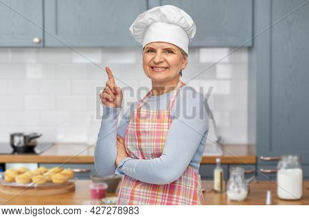 cooking, culinary and old people concept - portrait of smiling senior woman or chef in toque in apron pointing finger up over home kitchen background