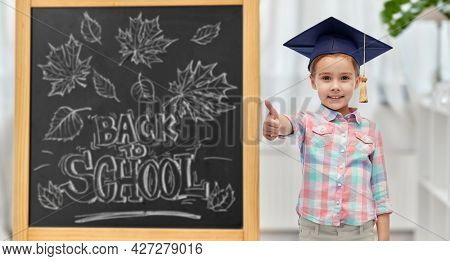 education, learning and people concept - happy little student girl with in bachelor hat or mortarboard showing thumbs up over chalkboard with back to school lettering on background