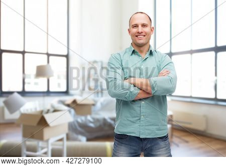 moving, real estate and people concept - smiling man with crossed arms over new home background