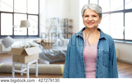 moving, real estate and people concept - smiling senior woman in denim shirt over new home background