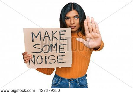 Young latin transsexual transgender woman holding make some noise banner with open hand doing stop sign with serious and confident expression, defense gesture