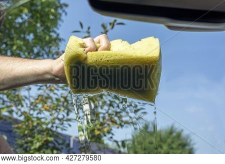 Wash The Windshield Of A Car With A Washcloth On A Sunny Day After A Flood,