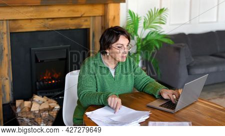 Senior Woman Is Filling Forms Whie Sitting In Front Of Laptop Monitor In Home Interior. Format Photo