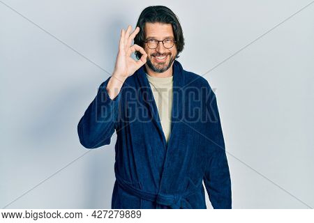 Middle age caucasian man wearing bathrobe and glasses smiling positive doing ok sign with hand and fingers. successful expression.