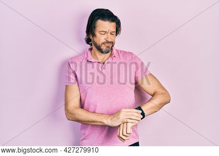 Middle age caucasian man wearing casual white t shirt checking the time on wrist watch, relaxed and confident