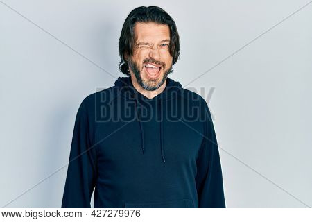 Middle age caucasian man wearing casual sweatshirt winking looking at the camera with sexy expression, cheerful and happy face.