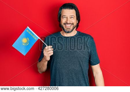 Middle age caucasian man holding kazakhstan flag looking positive and happy standing and smiling with a confident smile showing teeth